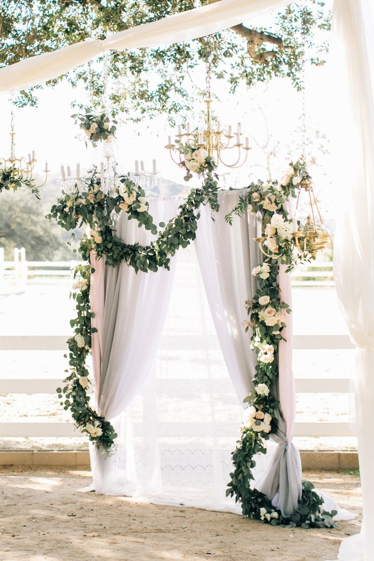 romantic hanging wedding backdrop ideas with olive branch, drapery and chandeliers
