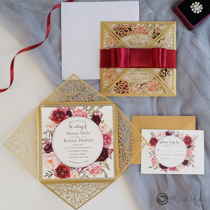 gold laser cut wrap with burgundy floral wedding invites and satin ribbon bow